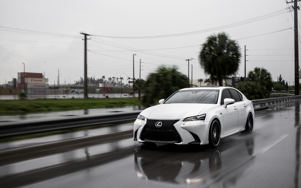 White Lexus driving on rainy road