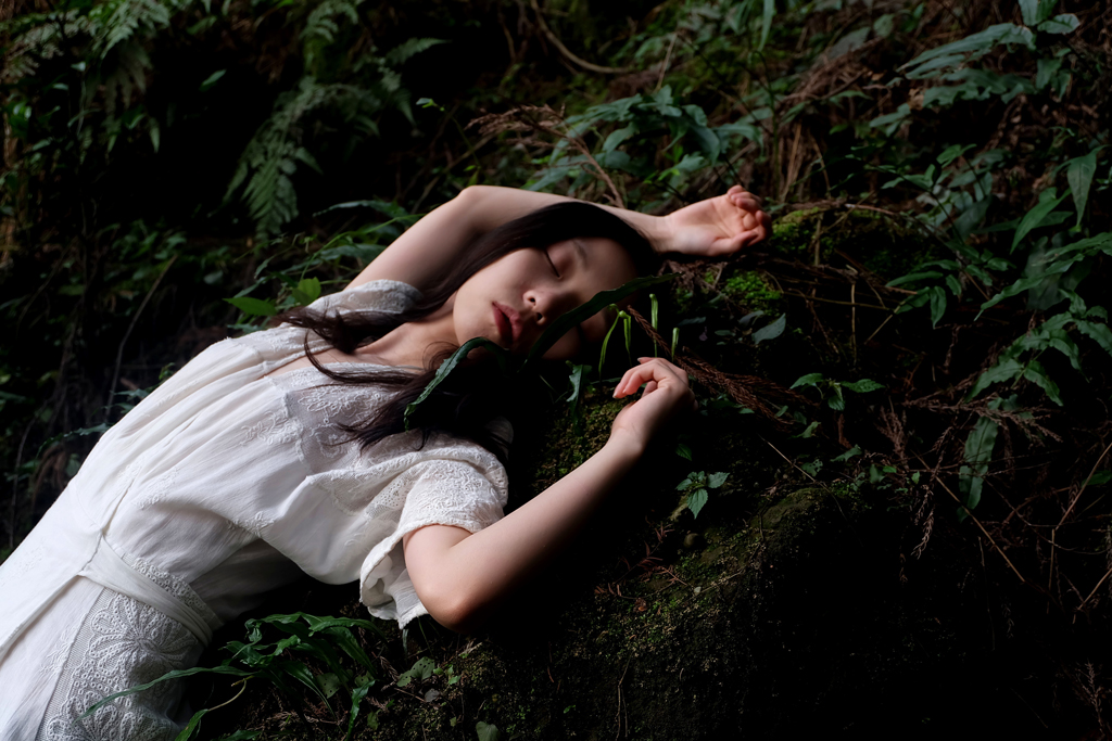 Woman in white lace dress laying on moss and leaves