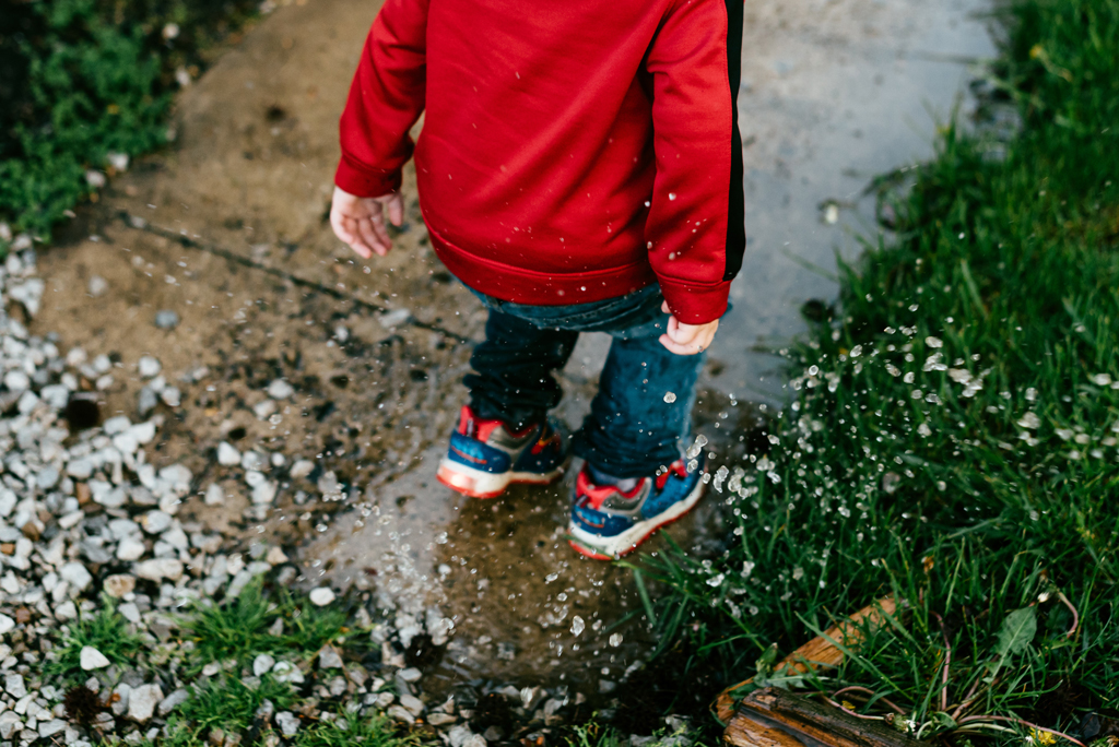 Aerial view of child in red sweatshirt jumping in a puddle on the sidewalk