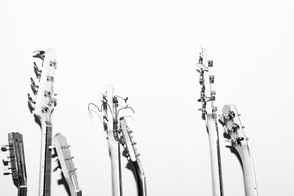 7 guitar heads propped up against a white wall