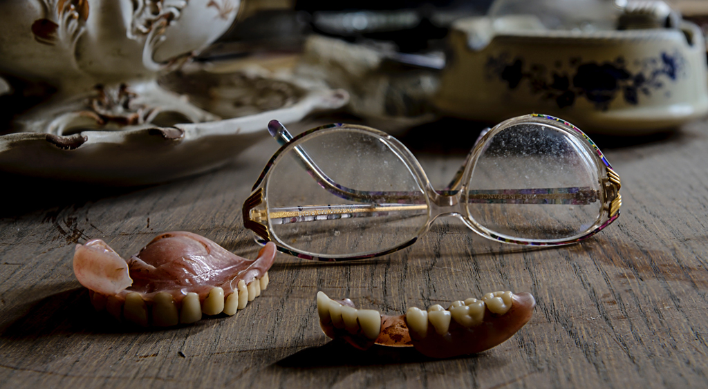 Eyeglasses, dentures, and old china plates laying on a wooden surface