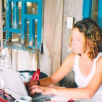 Photo of Jennifer Todhunter typing on her computer and smoking a cigarette