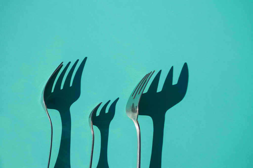 Three forks leaning against a teal blue background with their shadows behind them