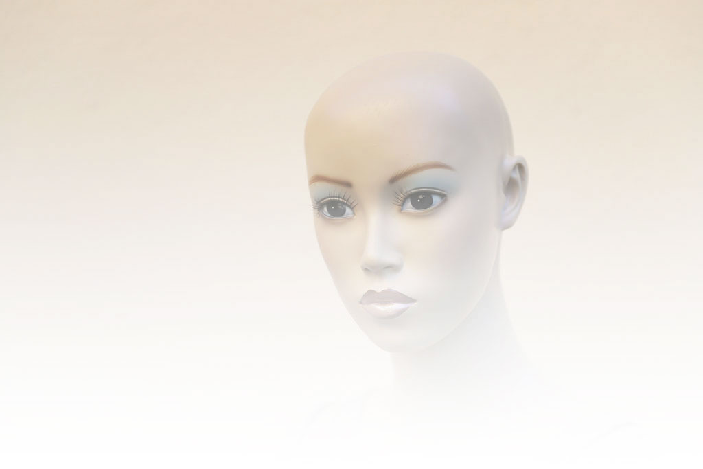 A bald mannequin with blue eyeshadow, blonde eyebrows, and pink lipstick looking to the side
