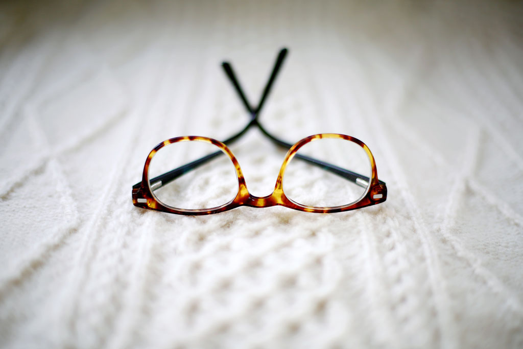 Tortoiseshell glasses on a white knit blanket