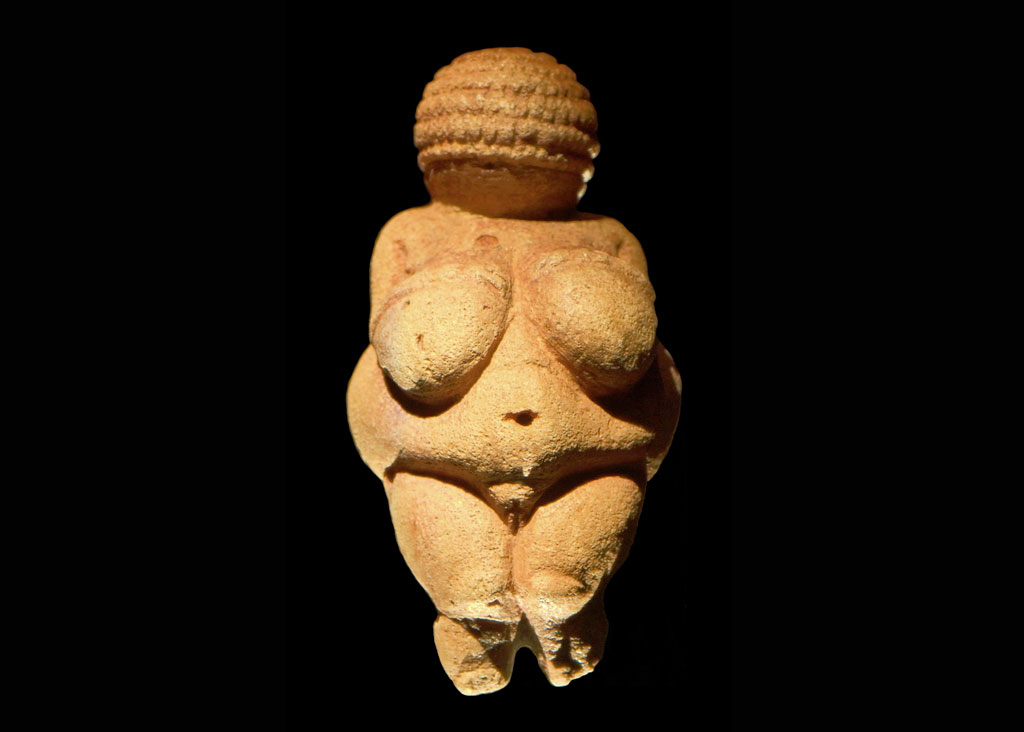Ancient sculpture of woman against black background