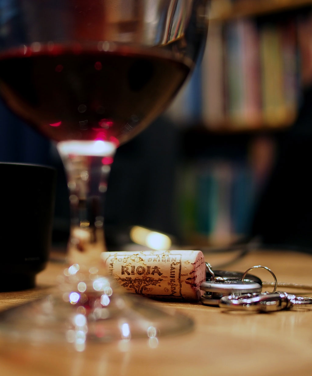 Glass of red wine in front of a cork and keys laying on a table