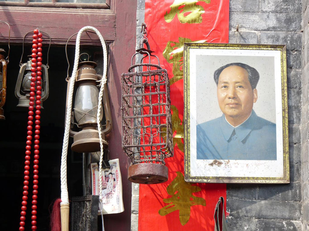 Framed photo of Mao Zedong, Former Chairman of the Peoples's Republic of China, hanging on a brick well next a flag and oil lanterns