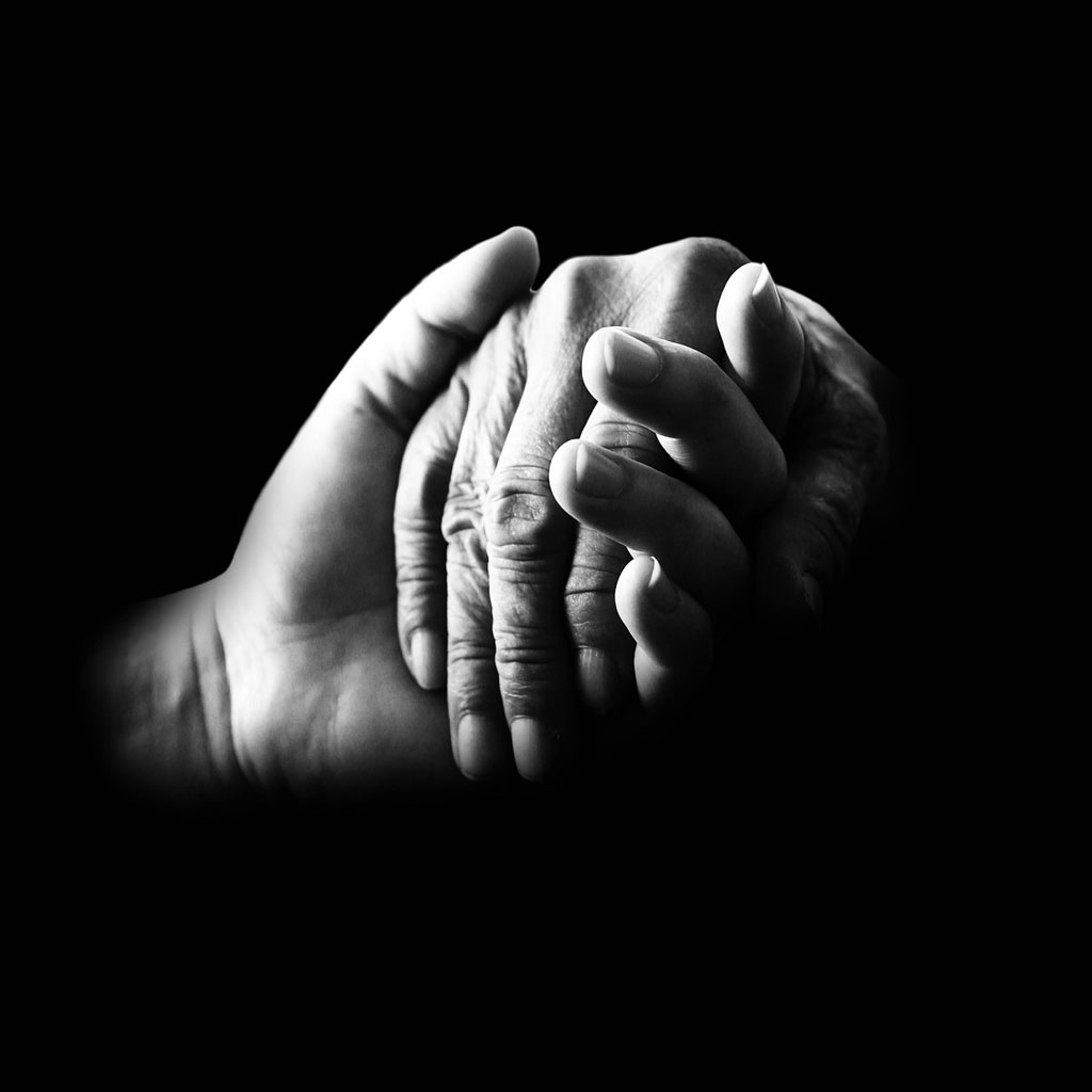 Black-and-white photo of two hands clasping each other