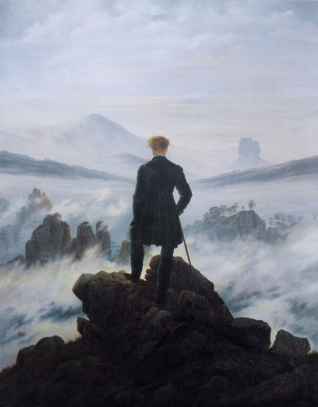 Man in a waistcoat standing on a cliff, holding a cane, and looking into a rocky valley covered in clouds