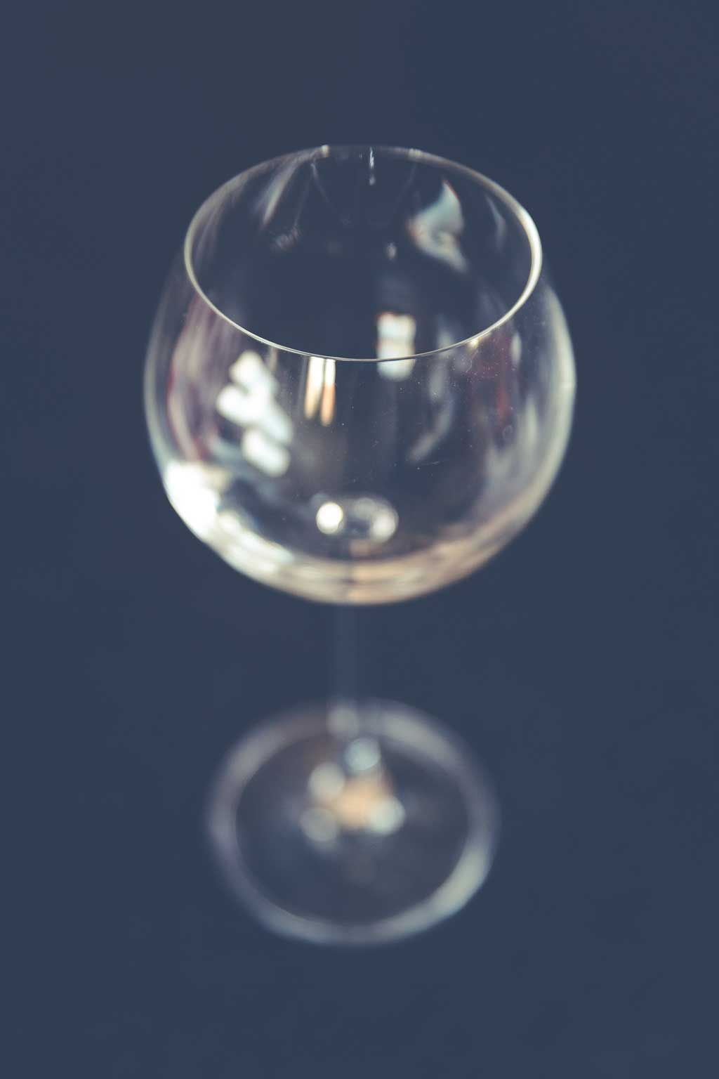empty wine glass in front of a blue background
