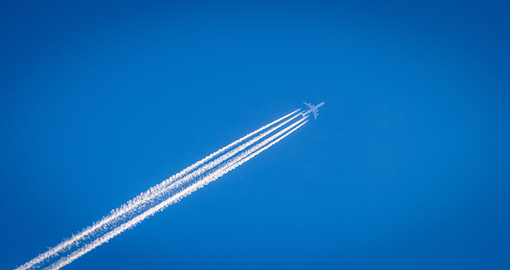 jet leaving a stream of contrail against a bright blue sky
