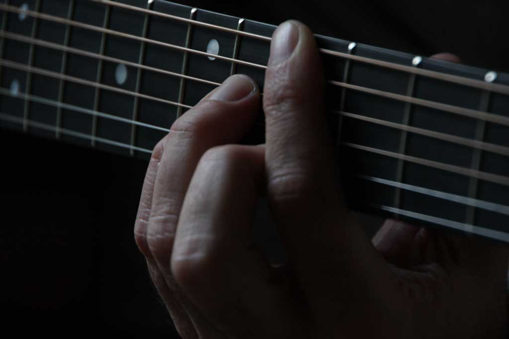 Fingers holding down a chord on an acoustic guitar