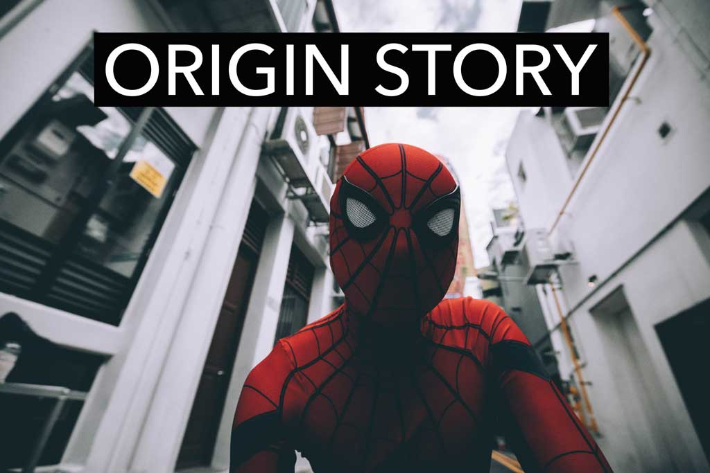 "Photograph of Spider Man with the title of the piece, ""Origin Story"" in bold lettering on the upper half of the photo"