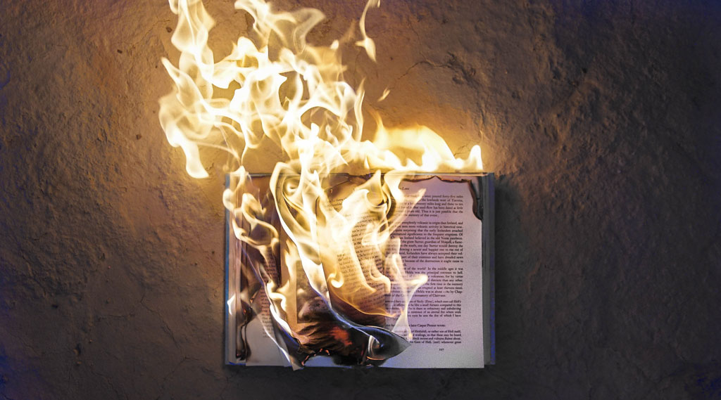 Photograph of a book that is on fire, positioned flat against the ground