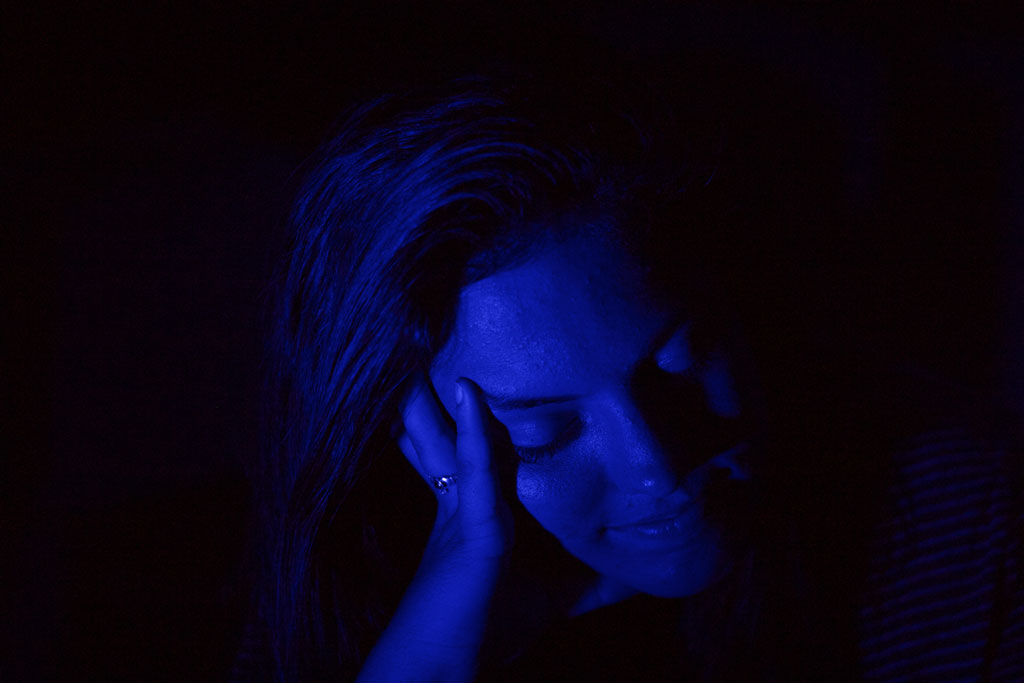 Woman looking down with blue light on her face