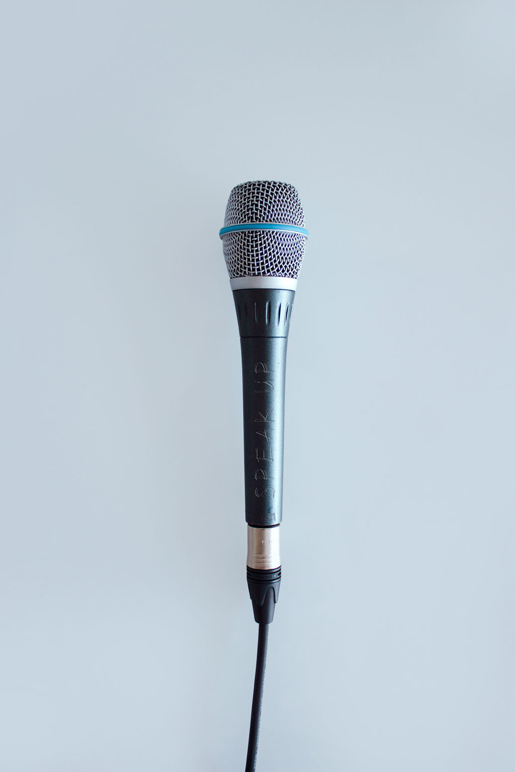 microphone with cord against pastel blue background