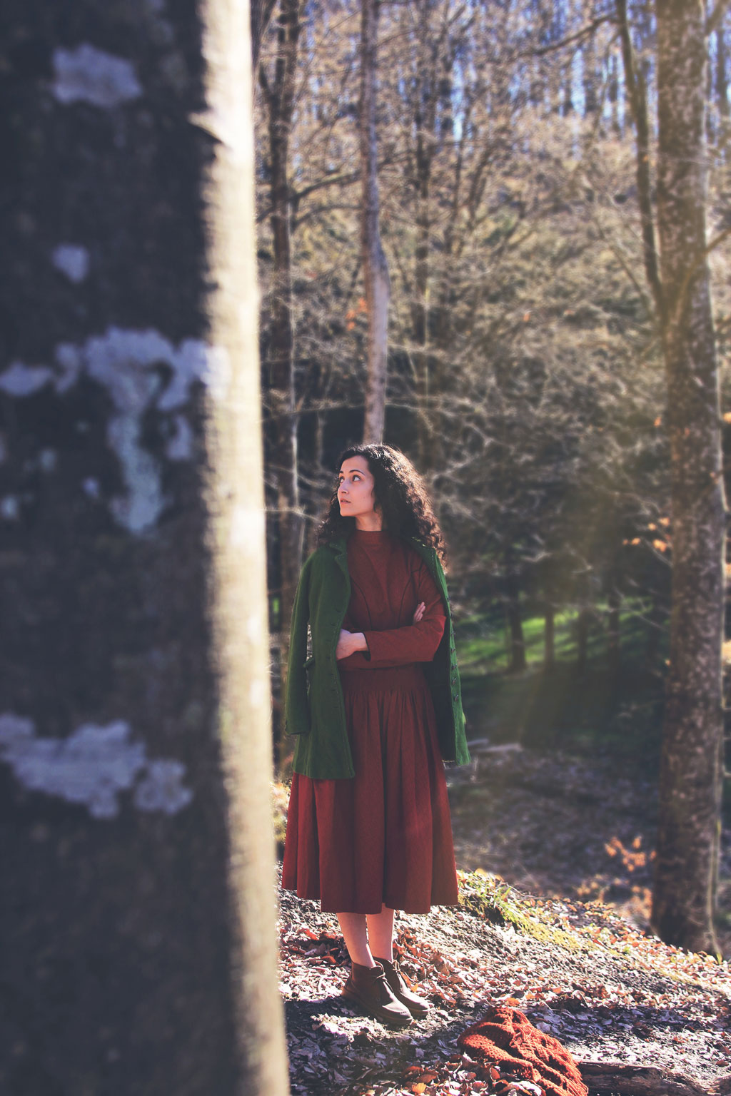 woman in red dress and green coat standing in forest, looking to the side
