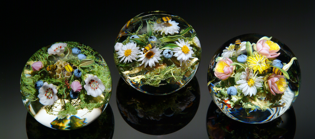 Three clear glass paperweights with ornamental flowers, grass, and bees inside them