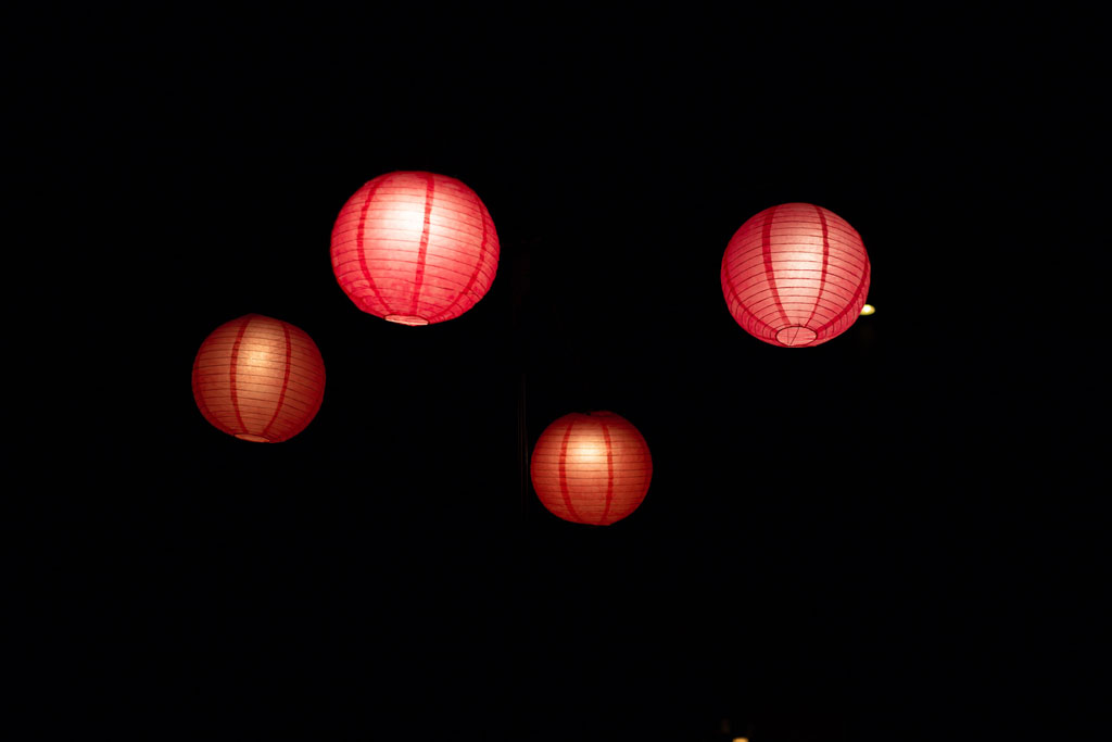Four red Chinese lanterns against a black background