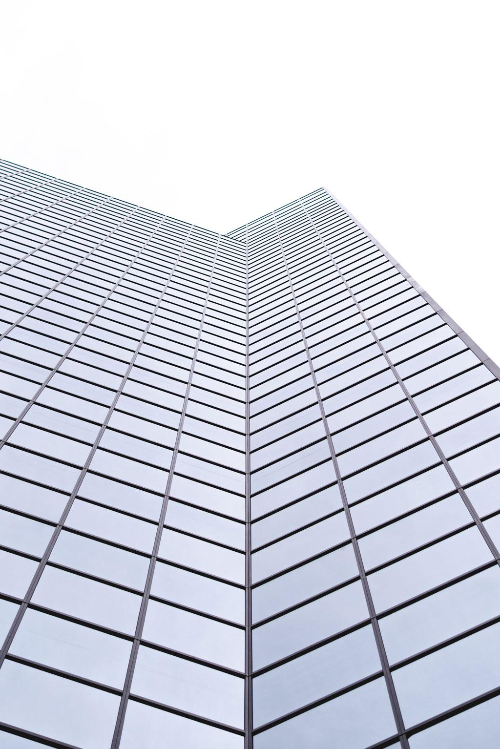 Skyscraper covered in windows against a white sky