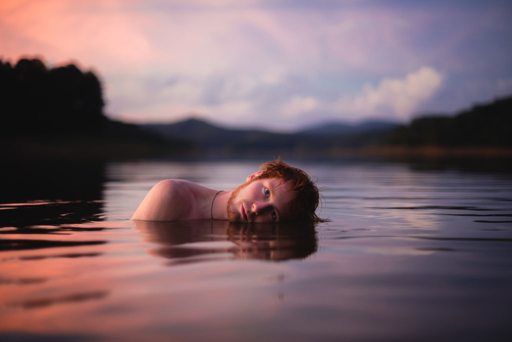 Man half-submerged in a lake during a pink sunset