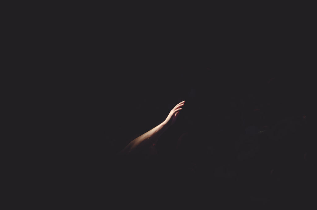 Man's arm upraised against a dark background