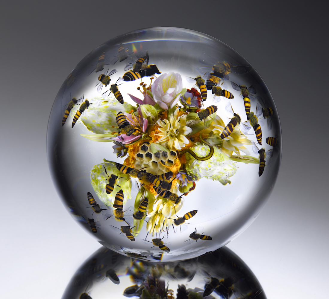 Clear glass sphere with flowers, bees, and a honeycomb inside it