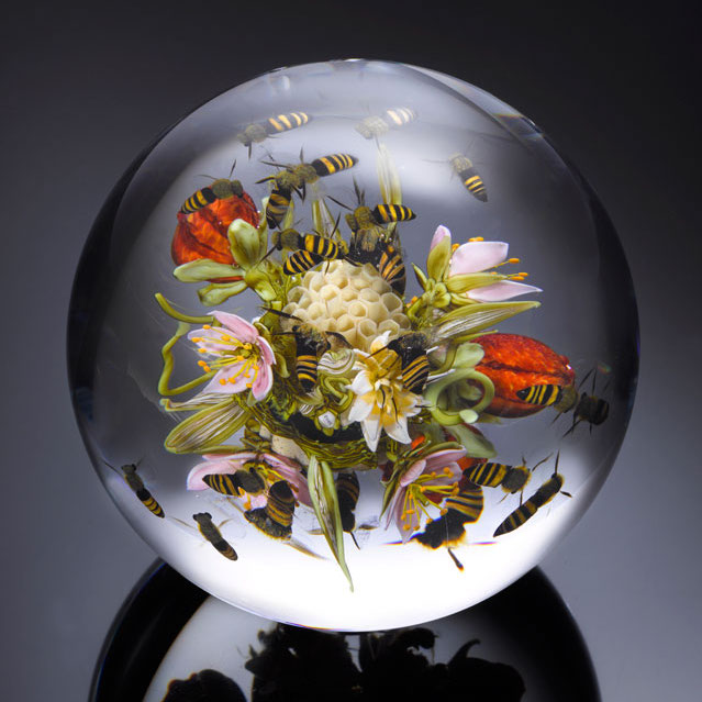 Clear glass sphere with flowers, bees, honeycomb, and fruit inside it
