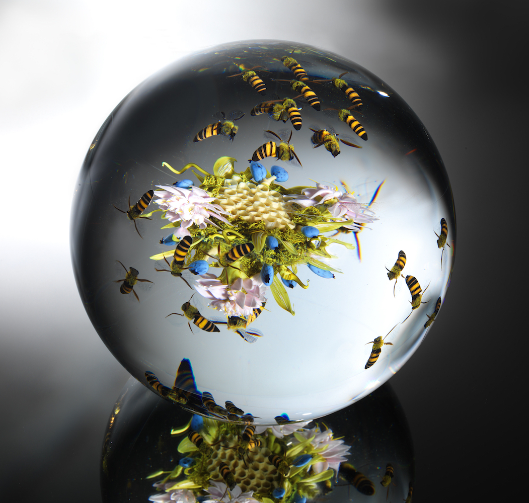 Clear glass sphere with figures of bees, flowers, grass, and a honeycomb inside it