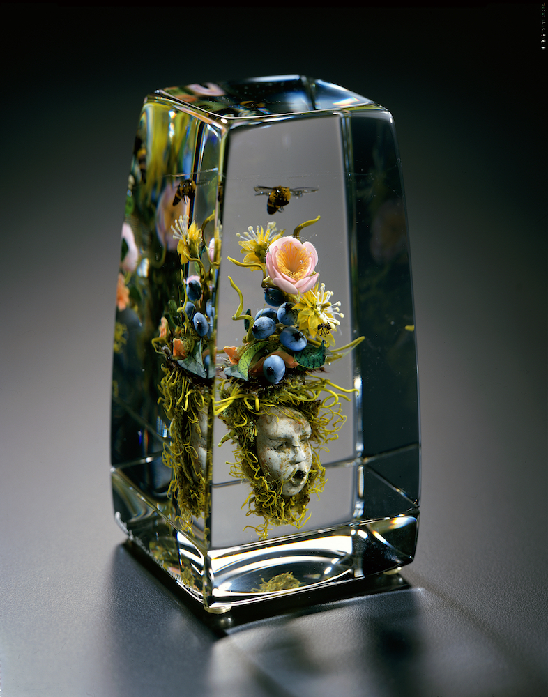 Clear glass rectangle with a mask inside it, topped with flowers, fruit, and one bee