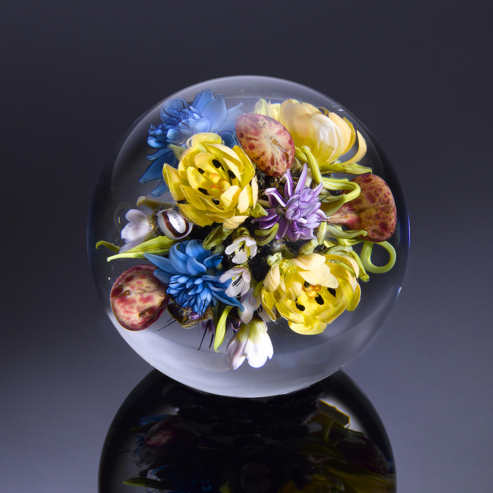 Clear glass sphere with bouquet of colorful flowers inside it