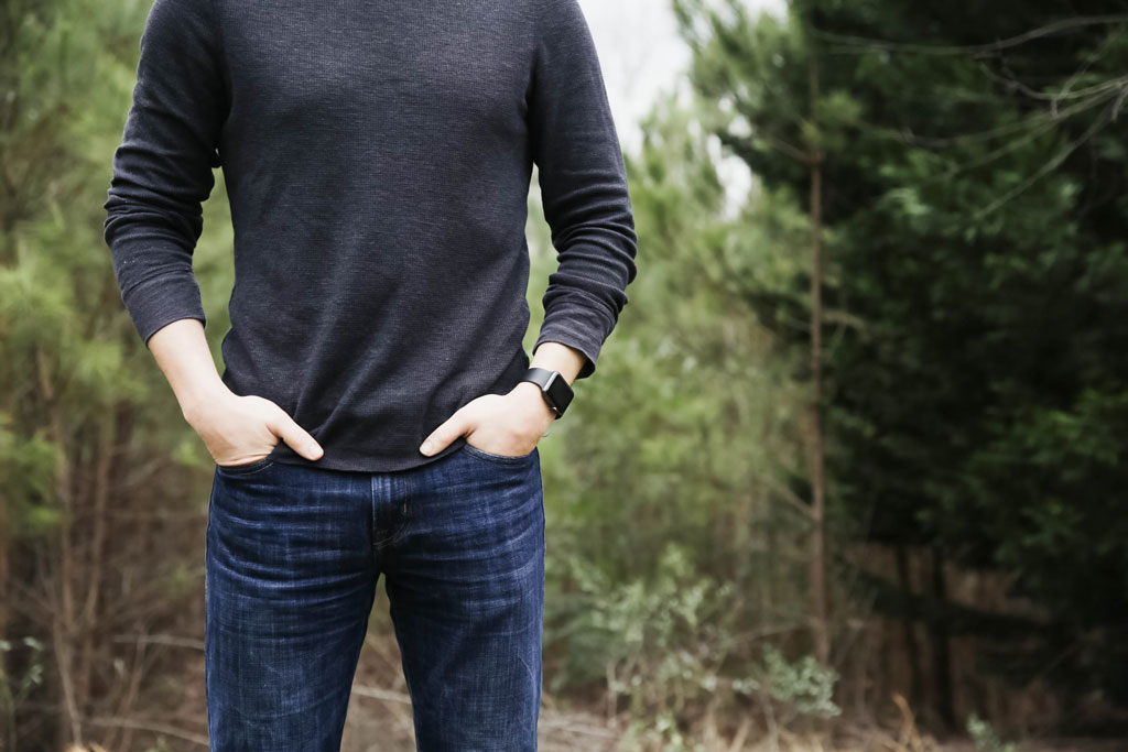 Man standing in forest with hand in his jean pockets
