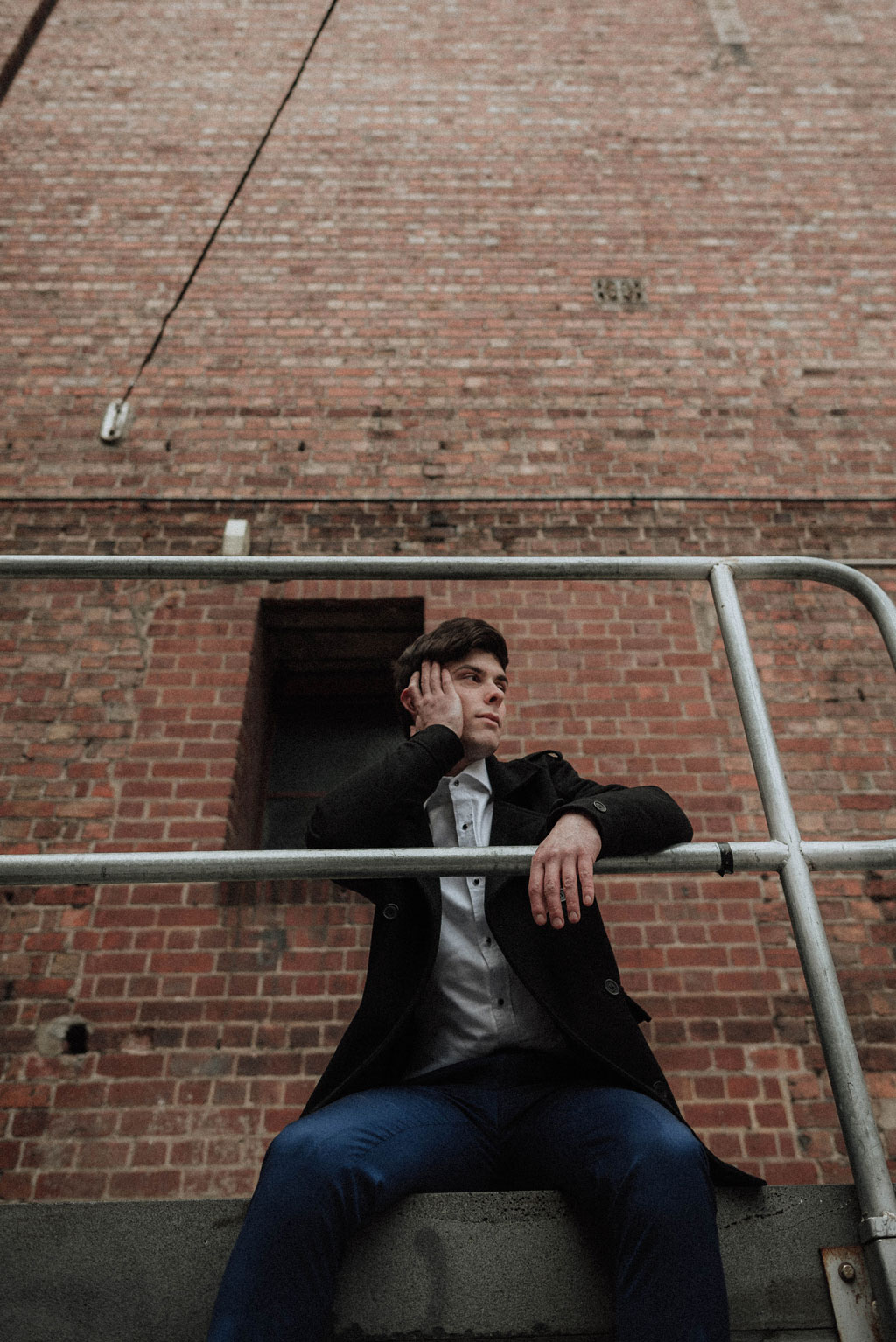 Young man with an arrogant expression on a fire escape