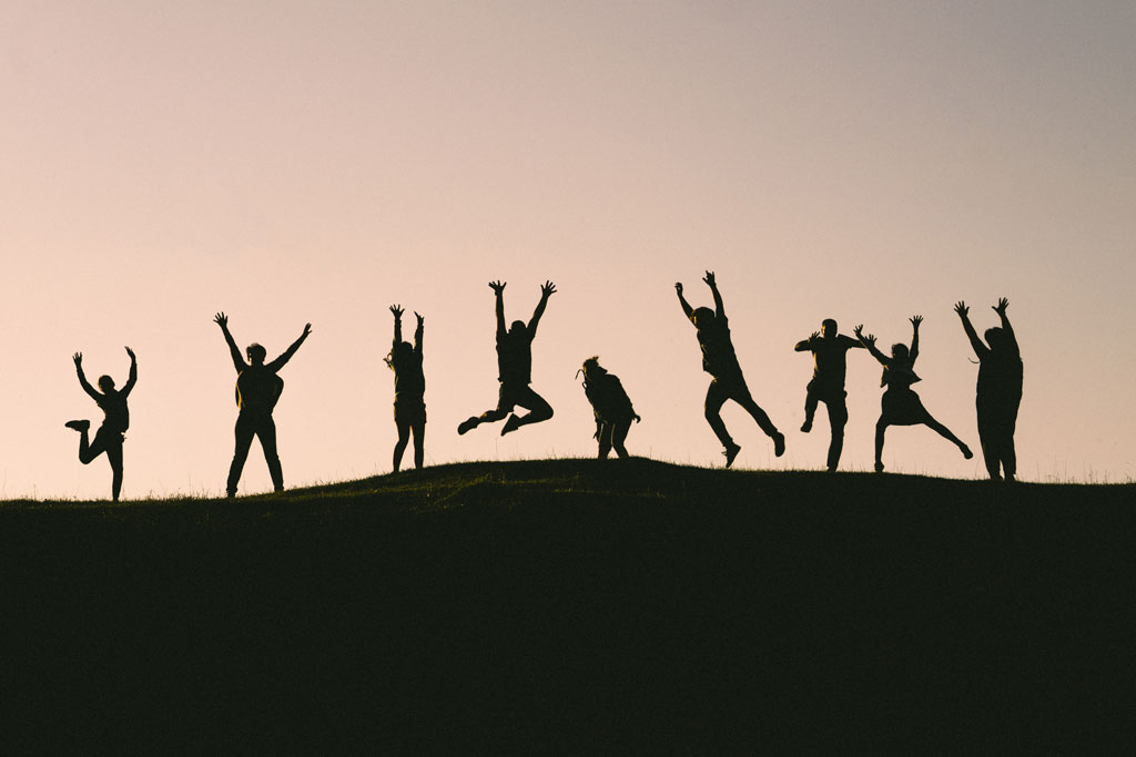 silhouette of children playing on a hill