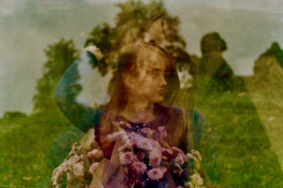 multiple exposure image of a woman against an outdoor background with a silhouette image and flowers