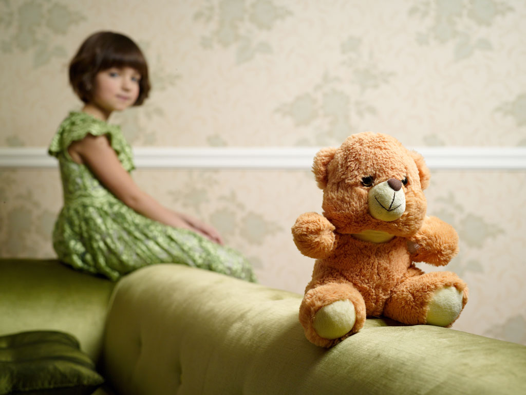 Little girl behind teddy bear, shallow focus