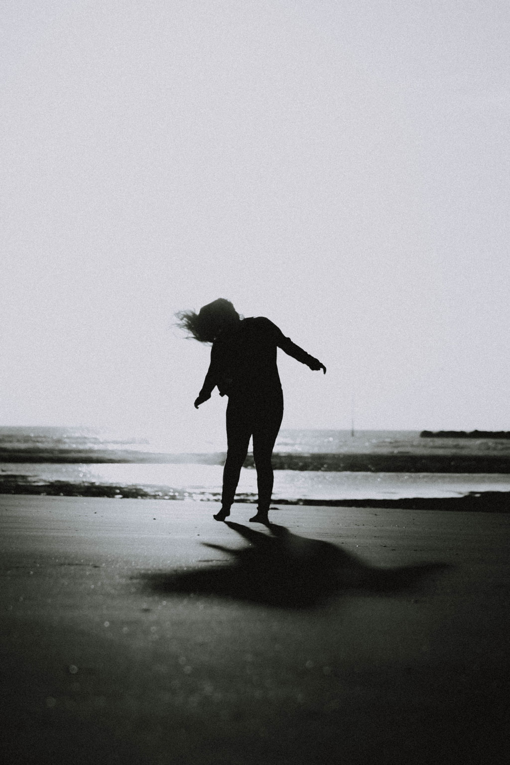 black and white image of a girl on the beach