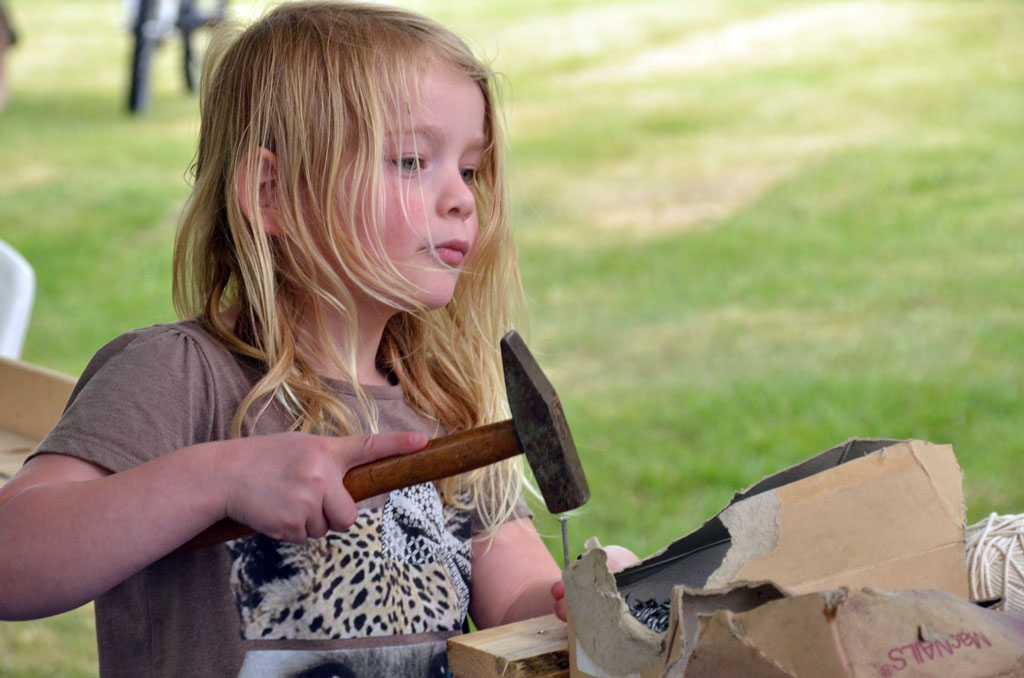 Little girl working with hammer