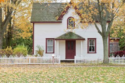 Picture of a victorian style house behind a white picket fence