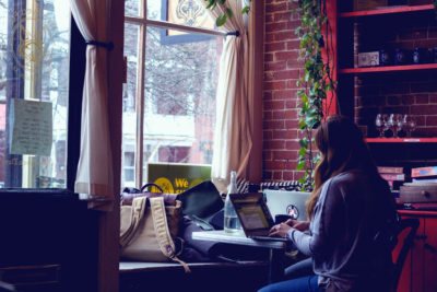 young woman sitting at a laptop in a window