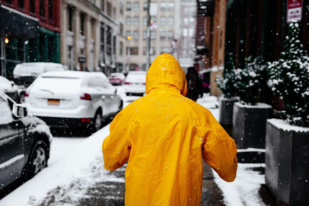 rear view of person in yellow slicker on snowy sidewalk