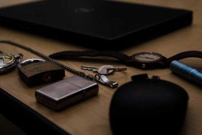 keys, lighter, pocket watch, watch, pen on a desktop in dim light