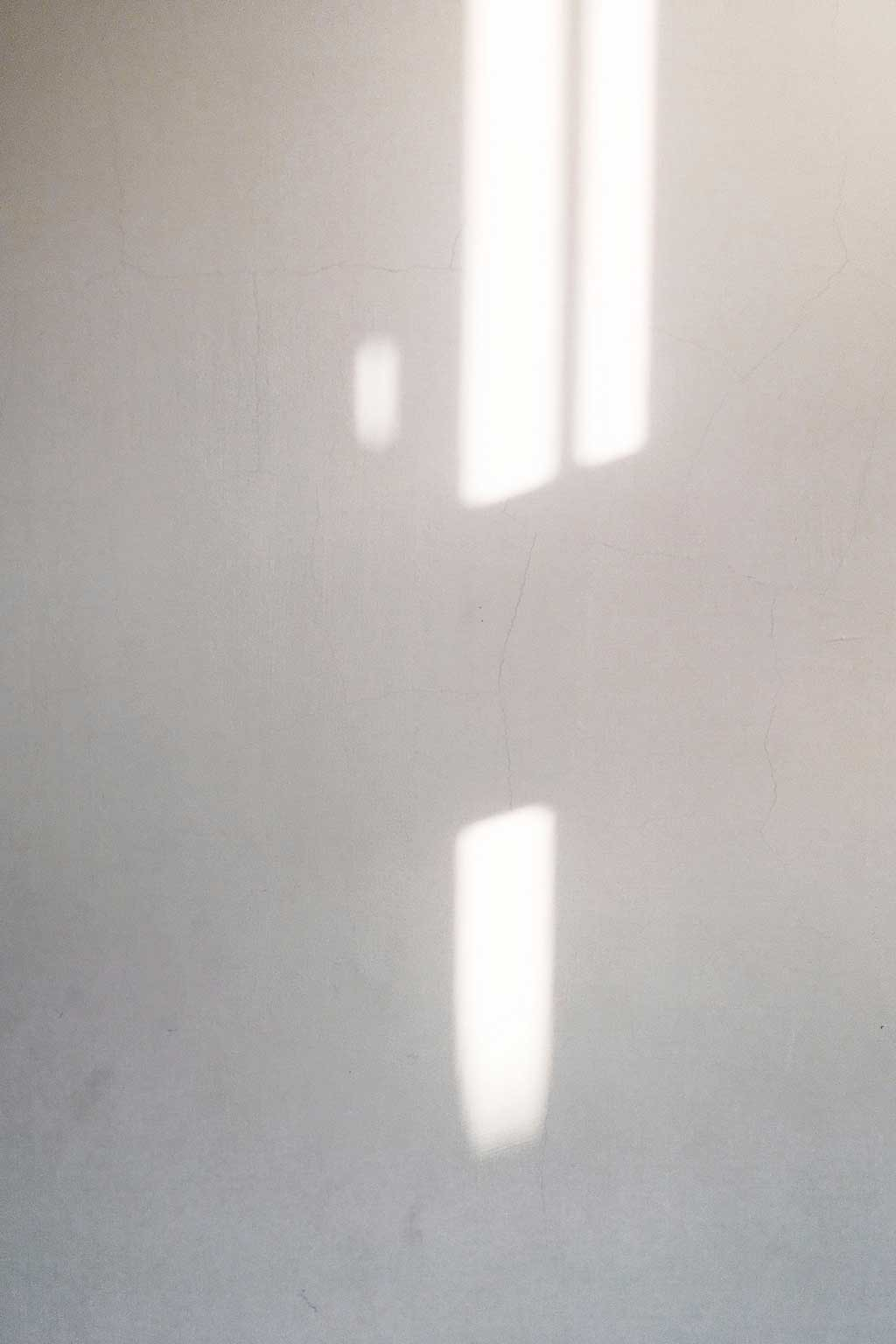a white wall with shadows and sunlight