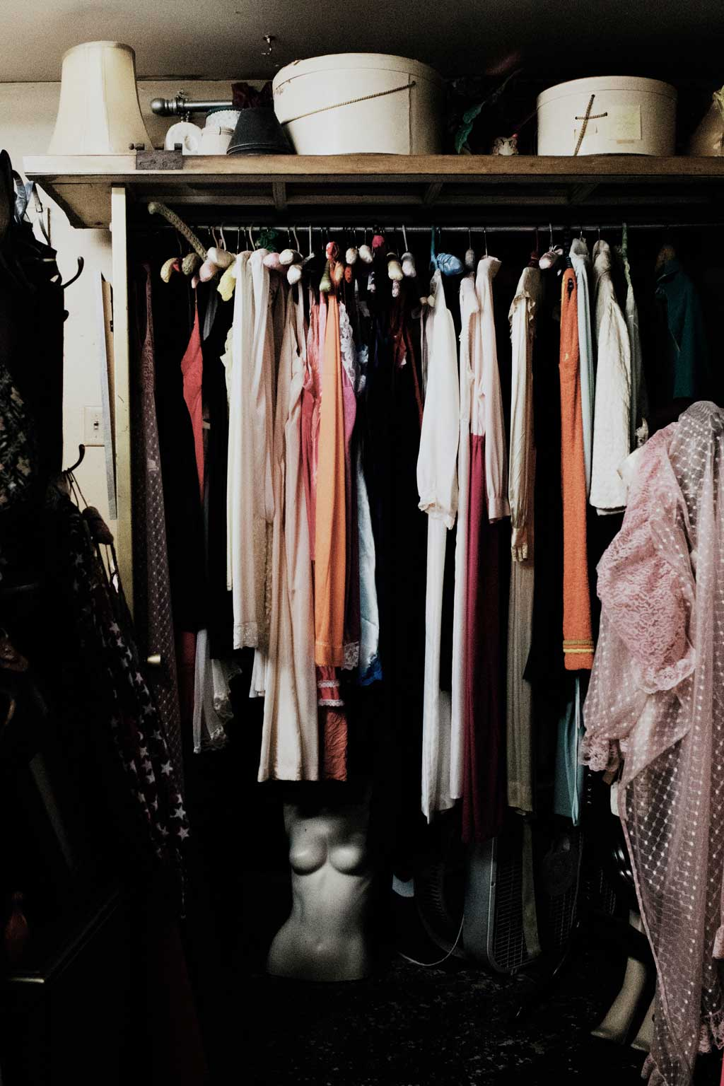 open closet with hanging clothes and the torso of a mannequin on the floor
