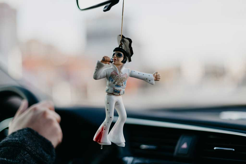 a plastic elvis figurine hanging from a car's rear view mirror
