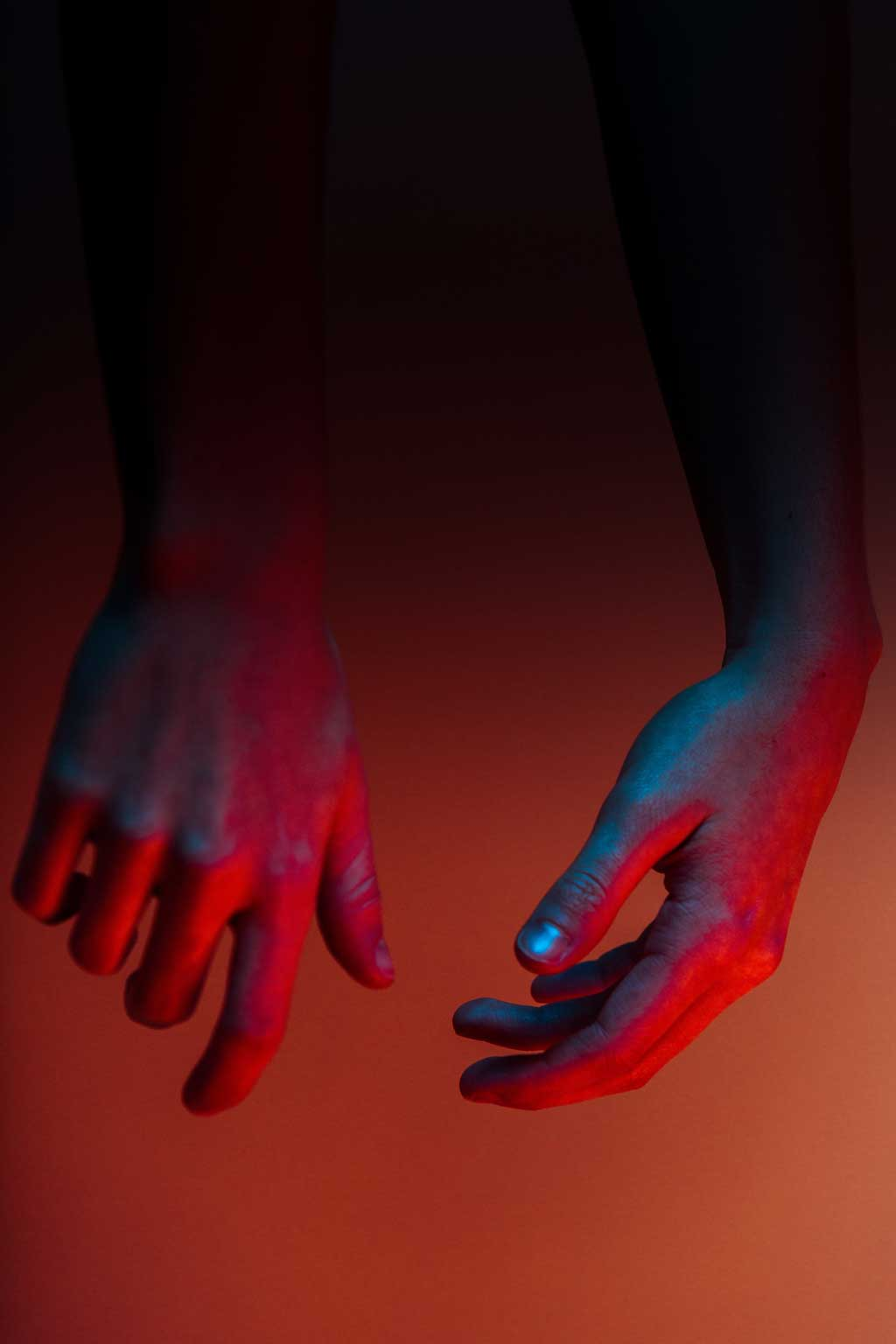 dangling hands bathed in red light