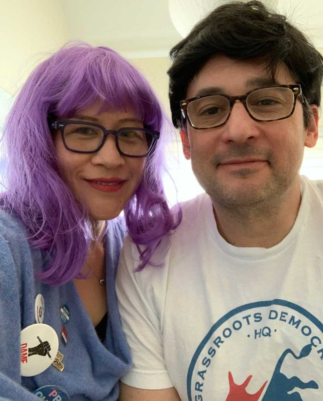 woman in long purple wig; man in shaggy black wig; political attire