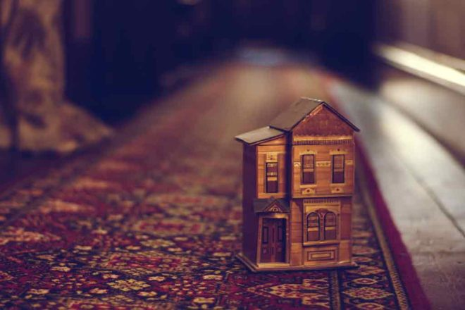 Miniature two-story house on patterned rug