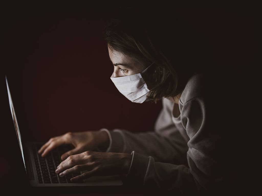 a woman typing furiously wearing a facemask